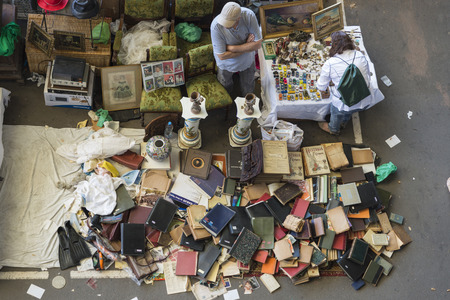 resale: Barcelona, Spain - June 18, 2014   Seller at his post of objects and furniture resale while a client is looking for something to buy in the most famous flea market in Barcelona, also known as Els Encants or Els Encants Vells, located in Glories neighborho Editorial