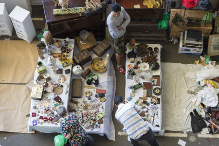 resale: Barcelona, Spain - June 18, 2014   Seller at his post of objects and furniture resale while two clients are looking for something to buy in the most famous flea market in Barcelona, also known as Els Encants or Els Encants Vells, located in Glories neighb
