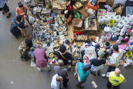 resale: Barcelona, Spain - June 18, 2014   Post of objects, antiques, and furniture resale while several clients are  looking for something to buy  in the most famous flea market in Barcelona, also known as Els Encants or Els Encants Vells, located in Glories nei Editorial