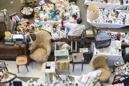 resale: Barcelona, Spain - June 18, 2014   Seller at his post of objects and furniture resale in the most famous flea market in Barcelona, also known as Els Encants or Els Encants Vells, located in Glories neighborhood  Seller at his post of objects and furniture Editorial