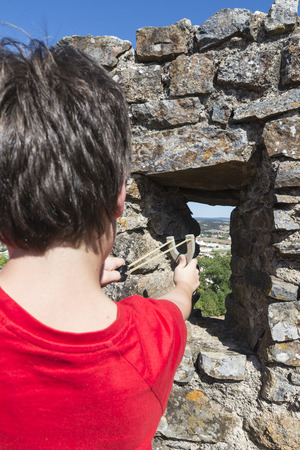 Ten-year-old is ready to fire his slingshot from the ramparts of a castle