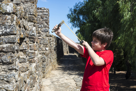 ramparts: Ten-year-old is ready to fire his slingshot from the ramparts of a castle