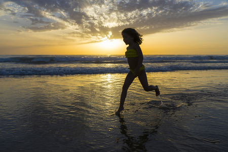 Little girl bathing on the beach at dusk on a beach in Andalusia, Spain photo