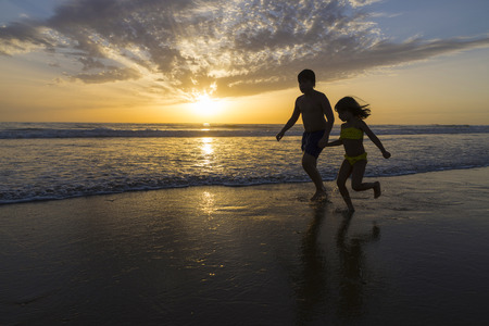 Children bathing on the beach at dusk on a beach in Andalusia, Spain photo