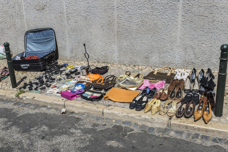 Lisbon, Portugal - August 19, 2014:  Objects used, clothes, bags, shoes and electronic equipment on a market stall in the most famous flea market in Lisbon, also known as Feira Da Ladra, located in the district of Alfama.Objects used, clothes, bags, shoes