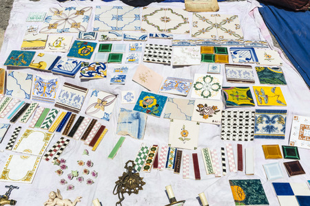 Lisbon, Portugal - August 19, 2014:  Objects used, tiles, artwork and ornaments on a market stall in the most famous flea market in Lisbon, also known as Feira Da Ladra, located in the district of Alfama.Objects used, tiles, artwork and ornaments on a mar