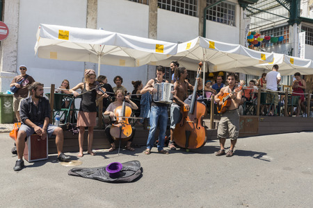 Lisbon, Portugal - August 19, 2014:  Band musicians playing in the most famous flea market in Lisbon, also known as Feira Da Ladra, located in the district of Alfama.Band musicians playing in flea market in Lisbon
