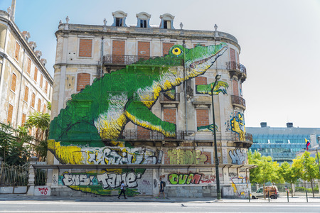 Lisbon, Portugal - August 17, 2014: Graffiti of a giant crocodile on the facade of an abandoned building.A boy and a girl walking down the street