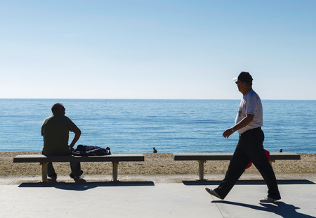 Barcelona, Spain - April 9, 2014:  several retirees strolling or sitting watching the sea on a promenade of Barcelona.