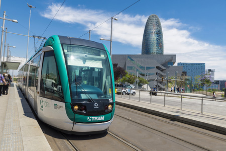 Barcelona, Spain - June 18, 2014: Barcelona tram known as Trambaix. The trambaix passing in the first term of the shot and in the second term is the agbar tower.