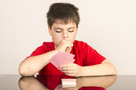 young boy smiling: Thoughtful young boy playing cards