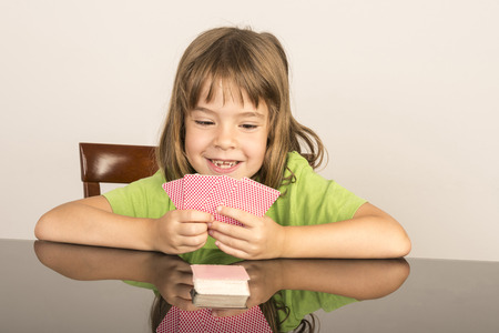portrait of smiling little girl playing cards