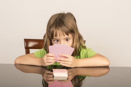 diverted: portrait of smiling little girl playing cards with squint