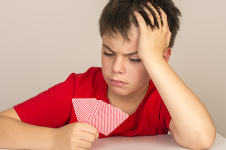 portrait of angry young boy playing cards Stock Photo