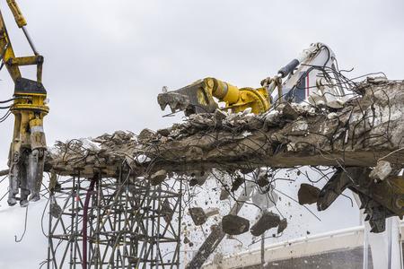 breaking down: Three cranes breaking down a bridge en la plaza de Les Glories, Barcelona.