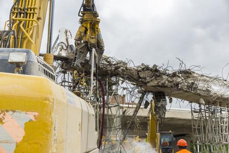 breaking down: Three cranes breaking down a bridge in square Les Glories, Barcelona.