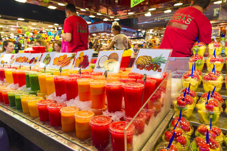 Barcelona, Spain - October 17, 2014: Fruit stand with chopped fruit and smoothies ready to take on the market of La Boqueria. Vendors are responding to their numerous customers