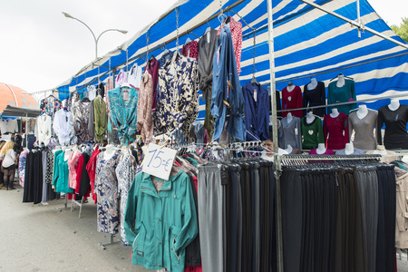 Badalona, Spain - November 1, 2014: Stall clothes in the market Turo Caritg in Badalona, a town next to Barcelona. The vendors serve customers while they choose and seek something you like