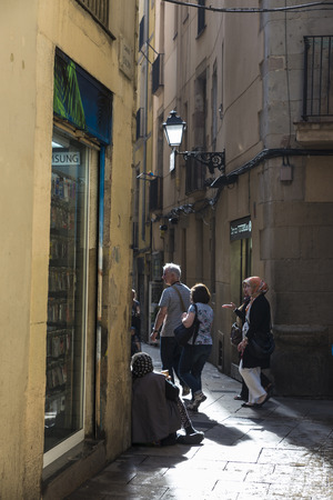 begs: Barcelona, Spain - October 17, 2014: A poor old woman begs for alms on a street of the old town of Barcelona known as Barri Gotic as people walk by your side