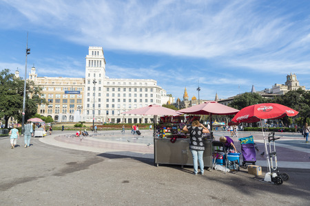 goodies: Barcelona, Spain - October 17, 2014: Placa Catalunya with its typical pigeons fluttering while tourists take pictures, walk or rest. In the foreground, one of the stalls of goodies