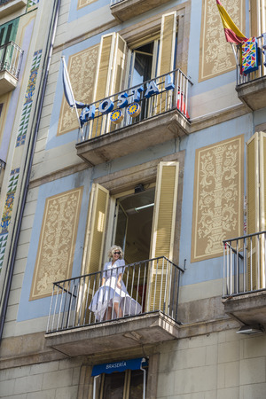 Barcelona, Spain - October 17, 2014: An actress imitates Marilyn Monroe on a balcony of a hotel in Les Rambles to attract customers