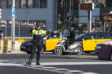 Barcelona, Spain - November 7, 2014: Police directing traffic in a square in Barcelona. This police force is called Guardia Urbana de Barcelona and one of its functions is to control the traffic in the city