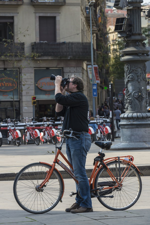 Barcelona, Spain - October 29, 2014: Cyclist standing on a walk taking a photograph Редакционное