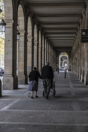 bourgeoisie: Barcelona, Spain - November 2, 2014: An elderly couple walks under the arches of Passeig Picasso, stately and French-inspired, are in the basement of several buildings housing built in the early twentieth century to the petty bourgeoisie of Barcelona Editorial