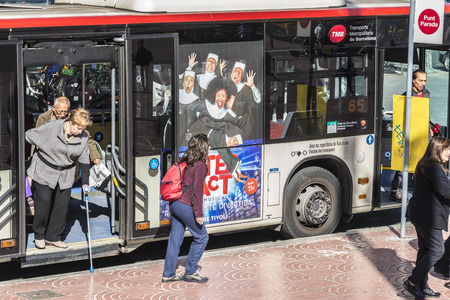 Barcelona, Spain - November 7, 2014: Bus passengers off at a bus stop. A woman who has difficulty walking off the bus aided by a stick