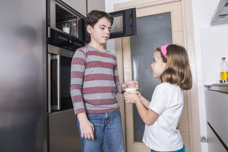 8 10 years: Children warming a glass of milk in the microwave