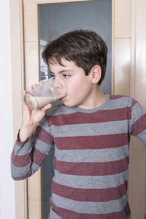 10 11 years: Young boy drinking a glass of chocolate milk