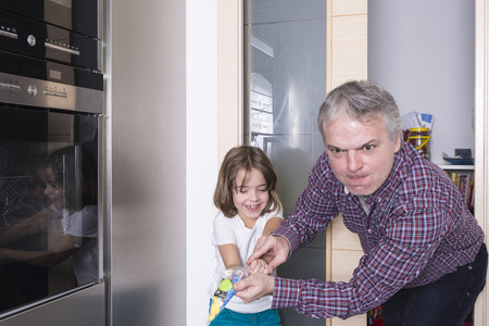 red handed: Father surprises his daughter taking candy Stock Photo