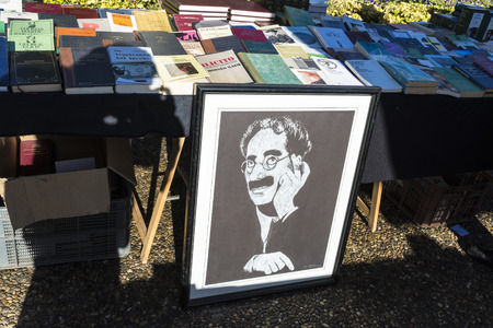 marx: Girona, Spain - December 28, 2014: Objects used, furniture, artwork and ornaments on a market stall in the flea market in Girona, also known as Mercat de la Lleona. This image highlights a drawing of Groucho Marx