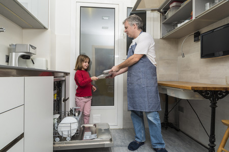 everyday scenes: Father and daughter together emptying the dishwasher Stock Photo