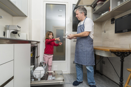 Father and daughter together emptying the dishwasher photo