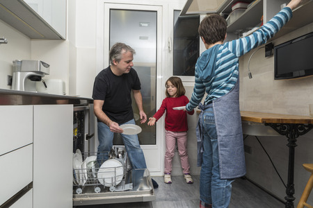 Father and sons together emptying the dishwasher
