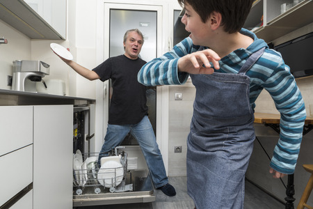 everyday scenes: Father and son joking while emptying the dishwasher