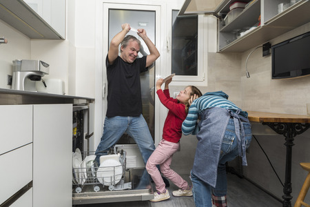 Father and sons joking while emptying the dishwasher photo