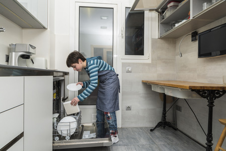 everyday scenes: Child emptying the dishwasher to help at home