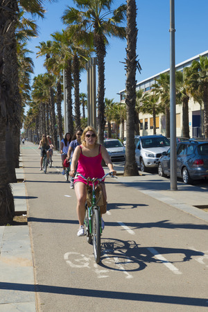 cycleway: Barcelona, Spain - April 7, 2014: People cycling on the promenade to Barceloneta beach