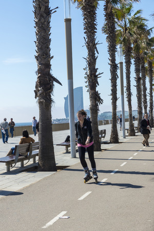 cycleway: Barcelona, Spain - April 7, 2014: Girl skating on the promenade to Barceloneta beach Editorial