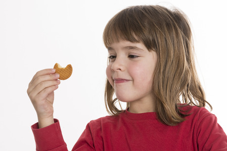 Meisje dat een cookie geïsoleerd op een witte achtergrond