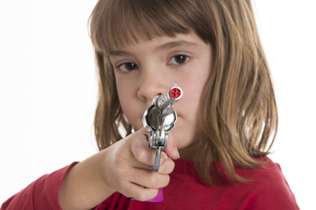 girl pointing: Little girl pointing a toy gun Stock Photo