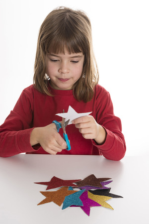 Little girl playing with stars made of paper with glitter colors photo