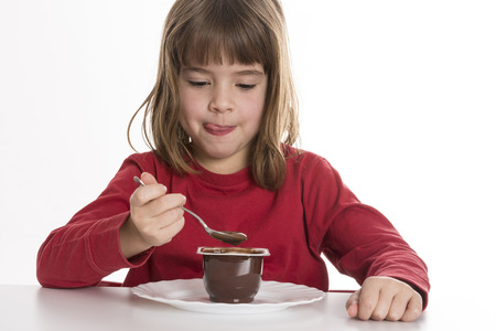 Little girl eating a chocolate custard isolated on white background photo