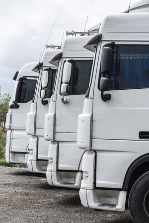 truck: Four white trucks of a transport company parked in a row Stock Photo