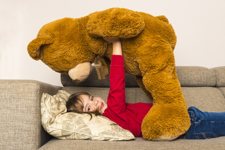 Little girl lying on sofa holding up her big teddy bear looking at camera photo