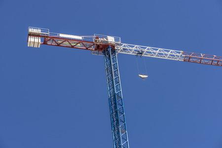 overhead crane: Construction crane blue, white and red against clear blue sky