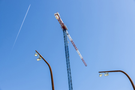 overhead crane: Construction crane with two modern streetlights and the trail of an airplane Stock Photo