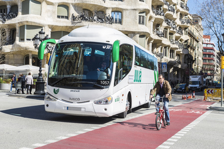 bike lane: Barcelona, Spain - March 27, 2015: A bus gives way to a bicycle circulating in the bike lane in front of the famous Casa Mila or La Pedrera building.  Coaches and bicycle traffic in front of the Casa Mila, better known as La Pedrera, designed by Antoni Ga